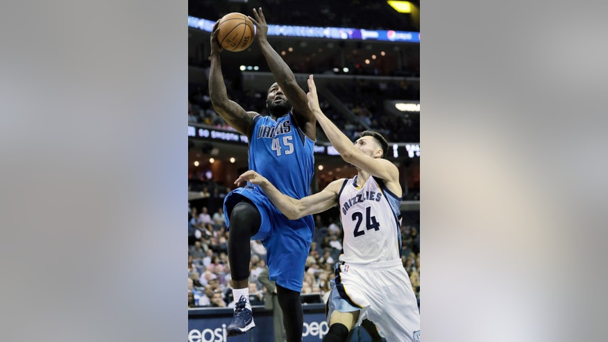 Dallas Mavericks' DeJuan Blair (45) goes to the basket over Memphis Grizzlies' Tony Gaffney during the first half of an NBA preseason basketball game in Memphis, Tenn., Wednesday, Oct. 9, 2013. (AP Photo/Danny Johnston)