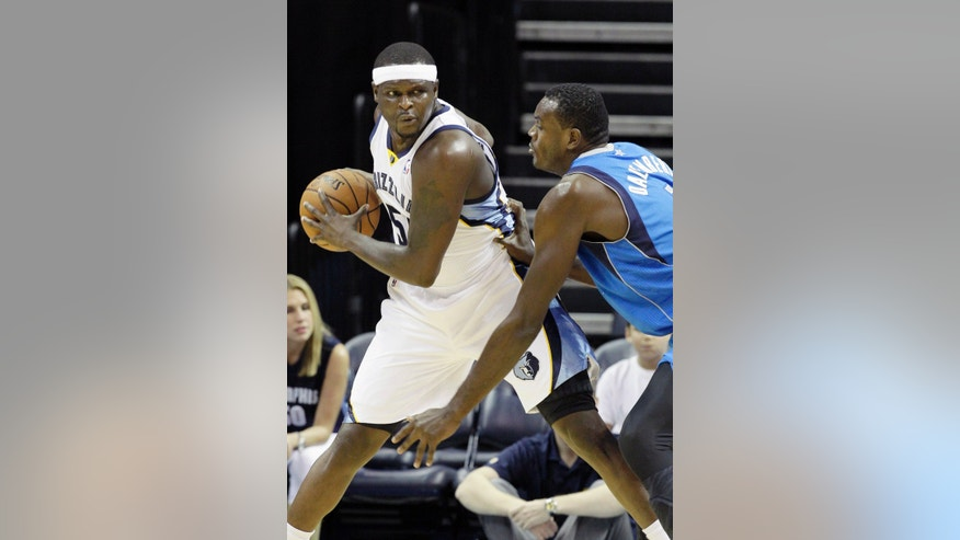 Memphis Grizzlies' Zach Randolph, left, is pressured by Dallas Mavericks' Samuel Dalembert during the first half of an NBA preseason basketball game in Memphis, Tenn., Wednesday, Oct. 9, 2013. (AP Photo/Danny Johnston)