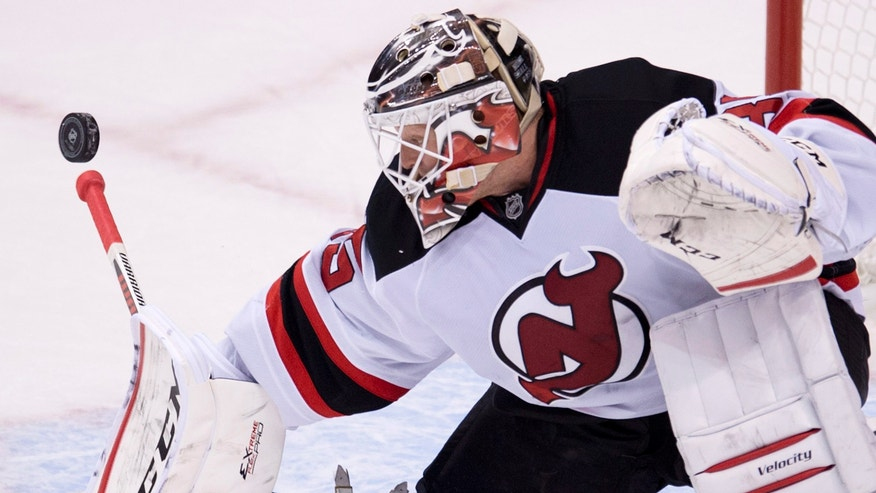 New Jersey Devils goalie Cory Schneider makes a save against the Vancouver Canucks during the second period of an NHL hockey game Tuesday, Oct. 8, 2013, in Vancouver, British Columbia. (AP Photo/The Canadian Press, Jonathan Hayward)