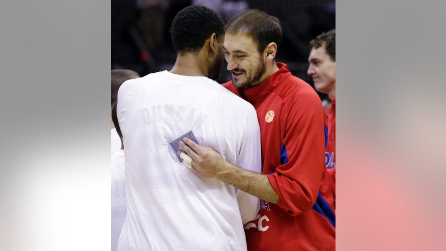 CSKA Moscow's Nedad Krstic, right, hugs San Antonio Spurs' Tim Duncan as the teams trade gifts prior to an exhibition NBA basketball game, Wednesday, Oct. 9, 2013, in San Antonio. (AP Photo/Eric Gay)
