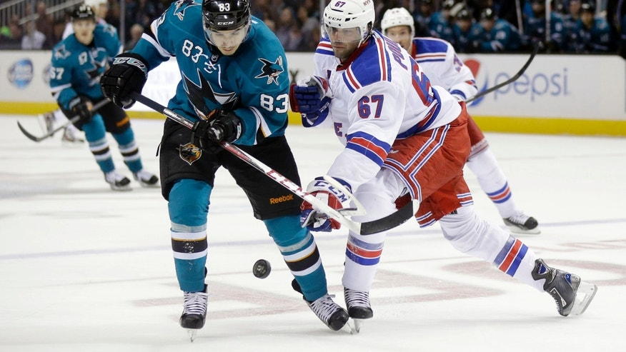 San Jose Sharks' Matt Nieto (83), left, is defended by New York Rangers' Benoit Pouliot (67) during the second period of an NHL hockey game on Tuesday, Oct. 8, 2013, in San Jose, Calif. (AP Photo/Marcio Jose Sanchez)
