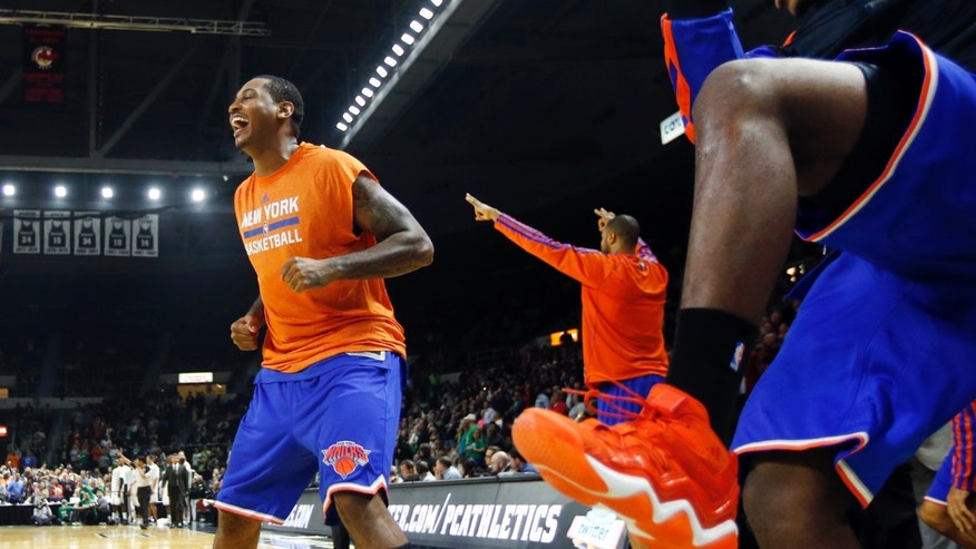New York Knicks forward Carmelo Anthony, left, and guard Iman Shumpert, right, celebrate on the bench in the last seconds of the Knicks' 103-102 victory over the Boston Celtics in a preseason NBA basketball game in Providence, R.I., Wednesday, Oct. 9, 2013. (AP Photo/Elise Amendola)