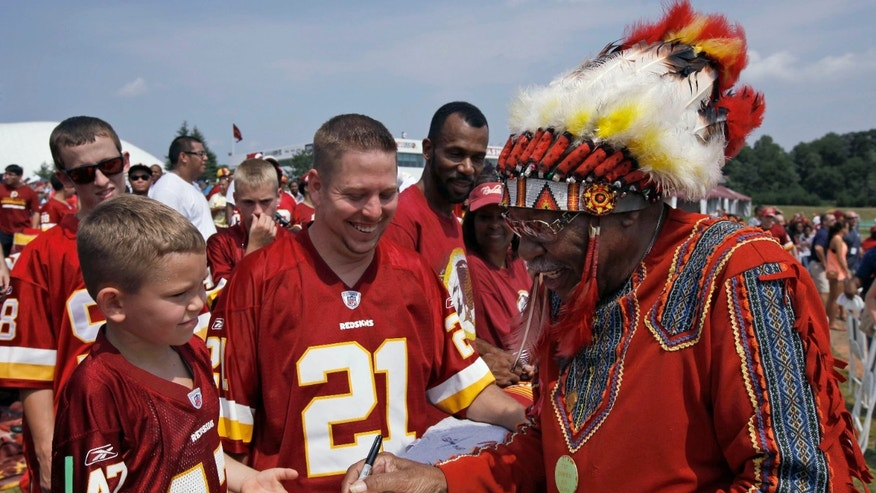 "FILE - In this Saturday, Aug. 4, 2012 file photo, Zena ""Chief Z"" Williams, unofficial mascot of the Washington Redskins, signs autographs during fan appreciation day at the Redskins' NFL football training camp at Redskins Park in Ashburn, Va. The name Washington Redskins has inspired protests, hearings, editorials, lawsuits, letters from Congress, even a presidential nudge. Yet behind the headlines, it's unclear how many Native Americans think ""Redskins"" is a racial slur. (AP Photo/Alex Brandon, File)"