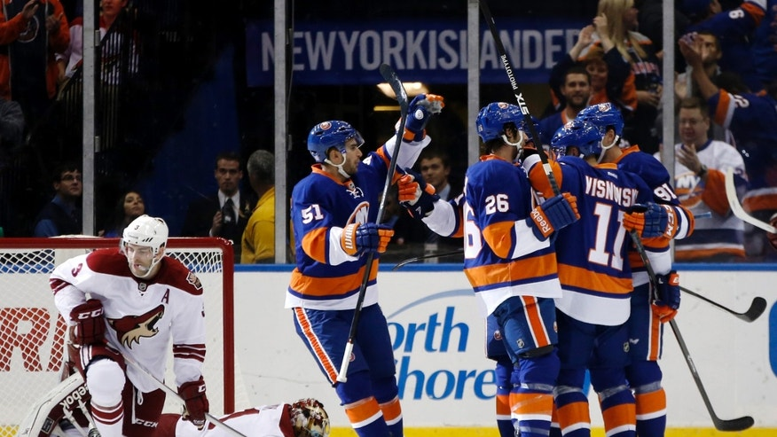 New York Islanders center Frans Nielsen (51), of Denmark, left wing Matt Moulson (26), defenseman Lubomir Visnovsky (11), of Slovakia, and center John Tavares (91) celebrate after Tavares scored in the first period of an NHL hockey game at Nassau Coliseum in Uniondale, N.Y., Tuesday, Oct. 8, 2013. (AP Photo/Kathy Willens)