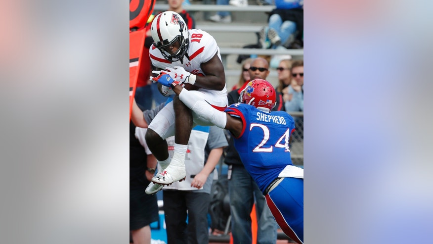 Texas Tech wide receiver Eric Ward (18) makes a catch while covered by Kansas cornerback JaCorey Shepherd (24) during the second half of an NCAA college football game in Lawrence, Kan., Saturday, Oct. 5, 2013. (AP Photo/Orlin Wagner)