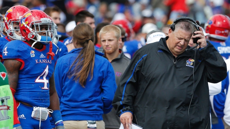 Kansas coach Charlie Weis, right, removes his head set during the second half of an NCAA college football game against Texas Tech in Lawrence, Kan., Saturday, Oct. 5, 2013. (AP Photo/Orlin Wagner)