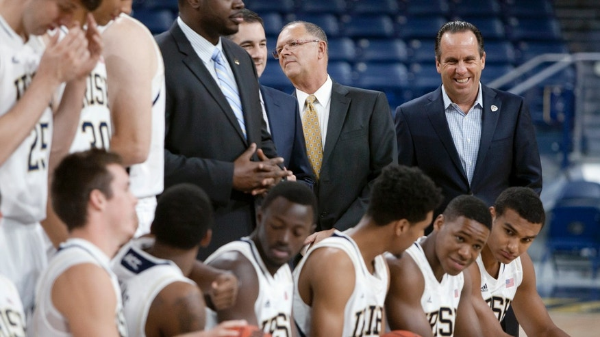 Notre Dame coach Mike Brey, right, laughs as his team gets into position for the official photograph during the NCAA college basketball team's media day, Wednesday, Oct. 9, 2013, in South Bend, Ind. (AP Photo/South Bend Tribune, James Brosher)