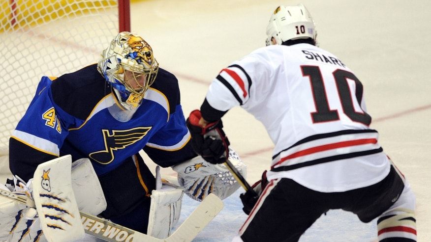 St. Louis Blues' goalie Jaroslav Halak, left, of Slovakia, blocks a shot by Chicago Blackhawks' Patrick Sharp (10) during the second period of an NHL hockey game Wednesday, Oct. 9, 2013, in St. Louis. (AP Photo/Bill Boyce)