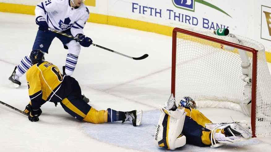 Toronto Maple Leafs left wing James van Riemsdyk (21) scores a goal against Nashville Predators goalie Pekka Rinne, of Finland, right, and Shea Weber (6) in the second period of an NHL hockey game on Thursday, Oct. 10, 2013, in Nashville, Tenn. (AP Photo/Mark Humphrey)