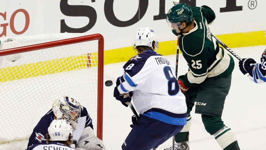 The puck glances off the glove of Minnesota Wild's Jonas Brodin (25) as he scores against Winnipeg Jets goalie Ondrej Pavelec, of the Czech Republic, in the first period of an NHL hockey game on Thursday, Oct. 10, 2013, in St. Paul, Minn. (AP Photo/Jim Mone)