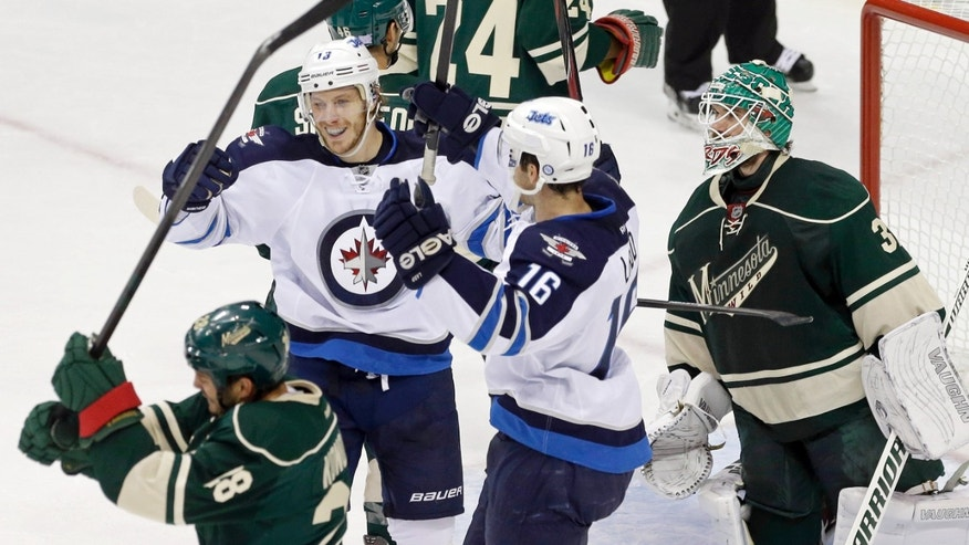 Winnipeg Jets' Bryan Little (18) and Andrew Ladd (16) celebrate Little's power-play goal off Minnesota Wild goalie Josh Harding, right, as Zenon Konopka, lower left, swings his stick toward the ice in the first period of an NHL hockey game on Thursday, Oct. 10, 2013, in St. Paul, Minn. (AP Photo/Jim Mone)