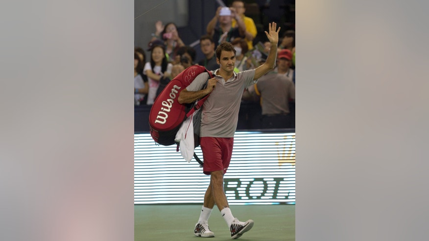 Switzerland's Roger Federer waves goodbye after losing to France's Gael Monfils in a match at the Shanghai Masters tennis tournament at the Qizhong Forest Sports City Tennis Center in Shanghai, China, Thursday, Oct. 10, 2013. Monfils won 6-4, 6-7, 6-3. (AP Photo/Ng Han Guan)