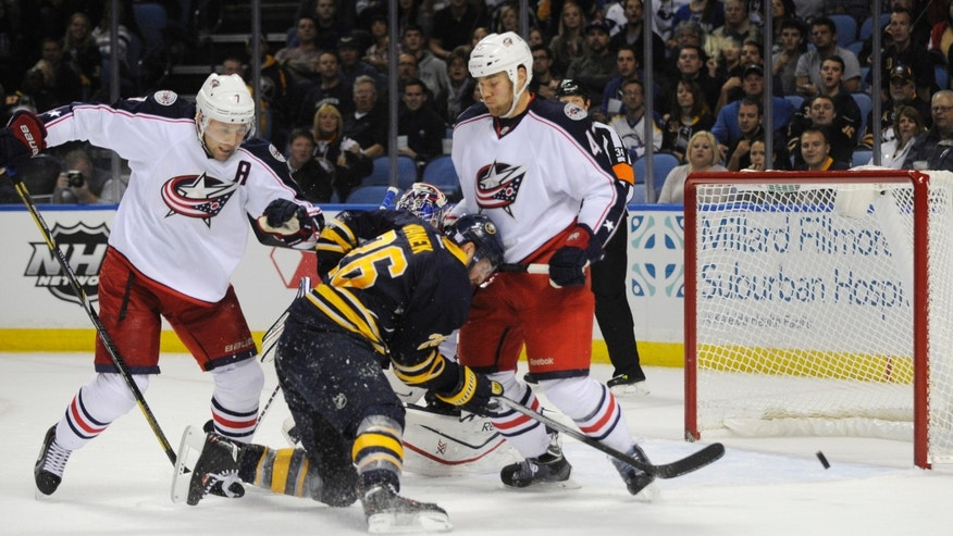 Buffalo Sabres' Thomas Vanek (26), of Austria, is checked as he shoots by Columbus Blue Jackets' Jack Johnson (7) and Dalton Prout (47) during the first period of an NHL hockey game in Buffalo, N.Y., Thursday, Oct. 10, 2013. (AP Photo/Gary Wiepert)