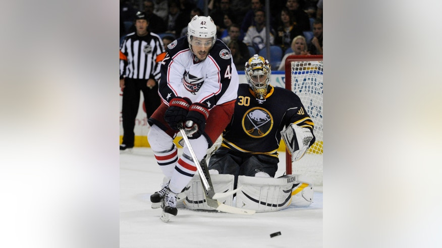 Columbus Blue Jackets center Artem Anisimov (42), of Russia, watches an incoming shot as Buffalo Sabres goaltender Ryan Miller (30) defends during the second period of an NHL hockey game in Buffalo, N.Y., Thursday, Oct. 10, 2013. (AP Photo/Gary Wiepert)