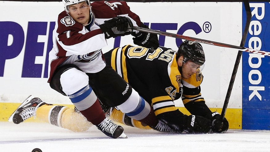 Colorado Avalanche's John Mitchell (7) eyes a loose puck after knocking down Boston Bruins' David Krejci during the first period of an NHL hockey game in Boston on Thursday, Oct. 10, 2013. (AP Photo/Winslow Townson)