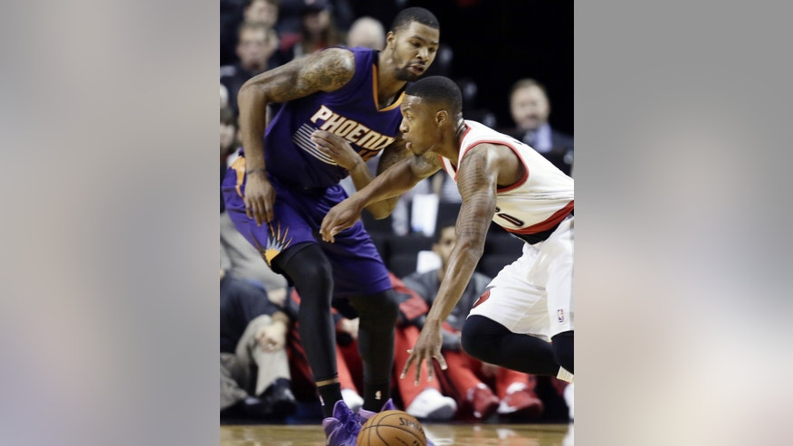 Portland Trail Blazers guard Damian Lillard, right, drives on Phoenix Suns forward Marcus Morris during the first half of an NBA preseason basketball game in Portland, Ore., Wednesday, Oct. 9, 2013. (AP Photo/Don Ryan)