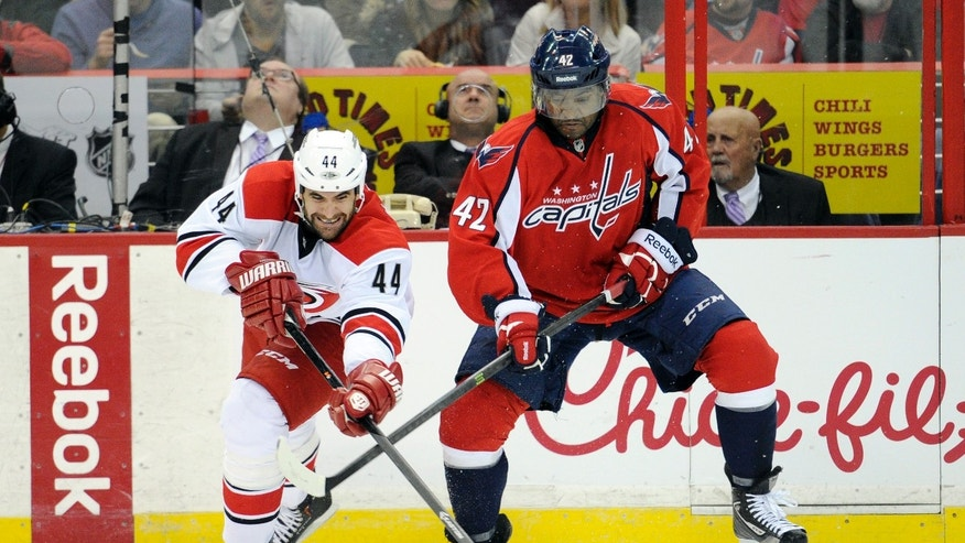 Carolina Hurricanes defenseman Jay Harrison (44) battles for the puck against Washington Capitals right wing Joel Ward (42) during the first period an NHL hockey game, Thursday, Oct. 10, 2013, in Washington. (AP Photo/Nick Wass)