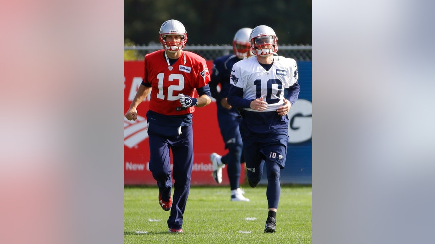 New England Patriots quarterback Tom Brady (12) and newly-acquired wide receiver Austin Collie (10) run during a stretching and drills session before NFL football practice begins at the team's facility in Foxborough, Mass., Wednesday, Oct. 9, 2013. The Patriots host the New Orleans Saints on Sunday. (AP Photo/Stephan Savoia)