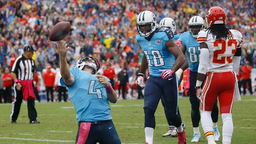 Tennessee Titans quarterback Ryan Fitzpatrick (4) celebrates after scoring a touchdown on a 9-yard run against the Kansas City Chiefs in the fourth quarter of an NFL football game on Sunday, Oct. 6, 2013, in Nashville, Tenn. Titans wide receiver Kenny Britt (18) runs up to Fitzpatrick as Chiefs safety Kendrick Lewis (23) walks away. (AP Photo/Wade Payne)