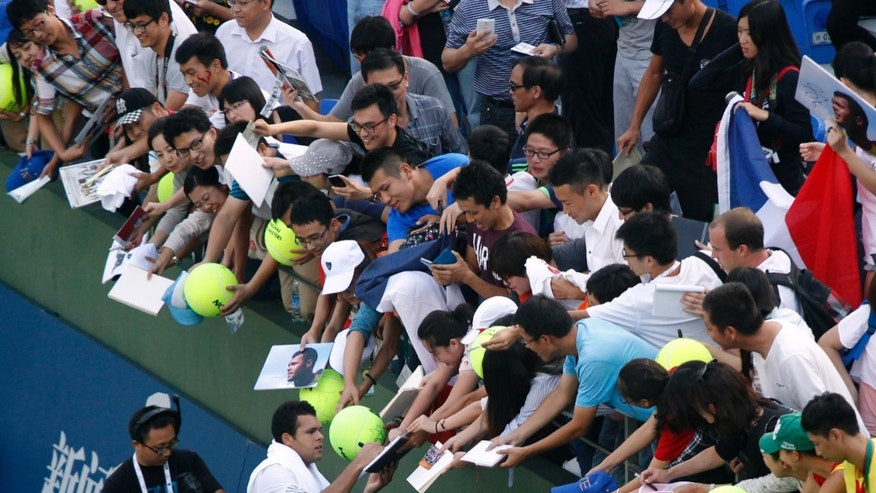 France's Jo-Wilfried Tsonga gives fans his autographs after defeating Japan's Kei Nishikori in the mens singles match of the Shanghai Masters tennis tournament at the Qizhong Forest Sports City Tennis Center in Shanghai, China, Thursday Oct 10, 2013. Tsonga won 7-6, 6-0.  (AP Photo)