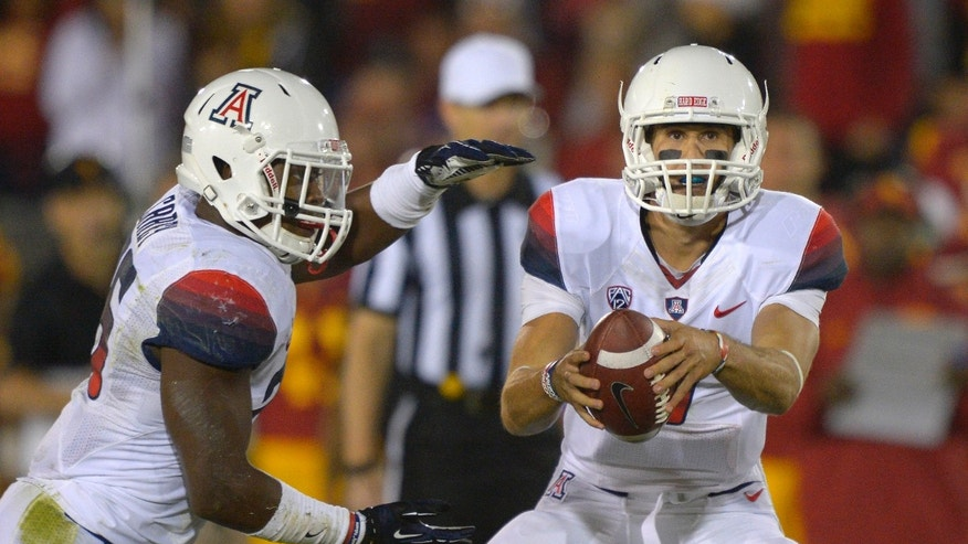 Arizona quarterback B.J. Denker, right, hands off to running back Ka'Deem Carey during the first half of an NCAA college football game against Southern California, Thursday, Oct. 10, 2013, in Los Angeles. (AP Photo/Mark J. Terrill)