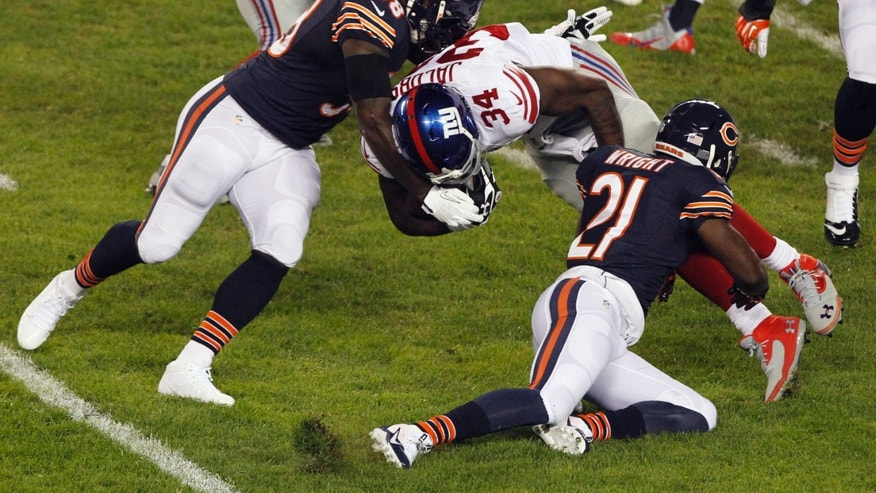 Chicago Bears linebacker D.J. Williams (58) and safety Major Wright (21) tackle New York Giants running back Brandon Jacobs (34) In the first half of an NFL football game, Thursday, Oct. 10, 2013, in Chicago. (AP Photo/Kiichiro Sato)