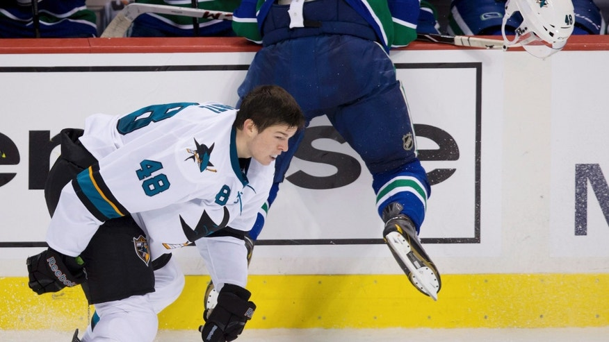 San Jose Sharks' Tomas Hertl, left, of the Czech Republic, loses his helmet as he collides with Vancouver Canucks' Alexander Edler, of Sweden, during the second period of an NHL hockey game in Vancouver, British Columbia, on Thursday, Oct. 10, 2013. (AP Photo/The Canadian Press, Darryl Dyck)