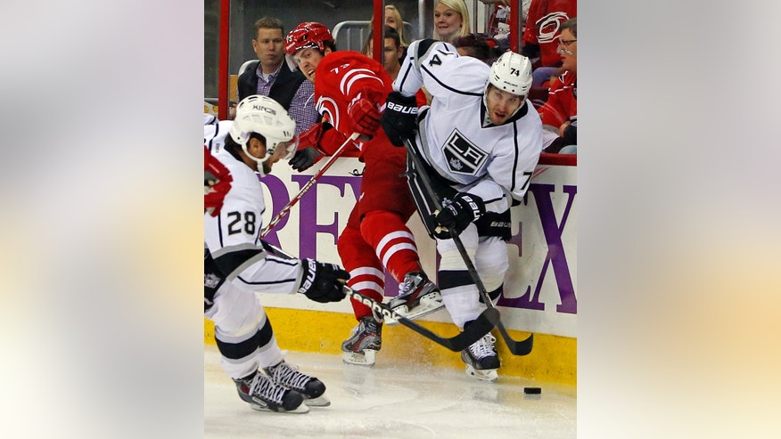Los Angeles Kings' Dwight King, right, competes with Carolina Hurricanes' Brett Bellemore (73) with Kings' Jarret Stoll (28) nearby during the first period of an NHL hockey game, Friday, Oct. 11, 2013, in Raleigh, N.C. (AP Photo/Karl B DeBlaker)