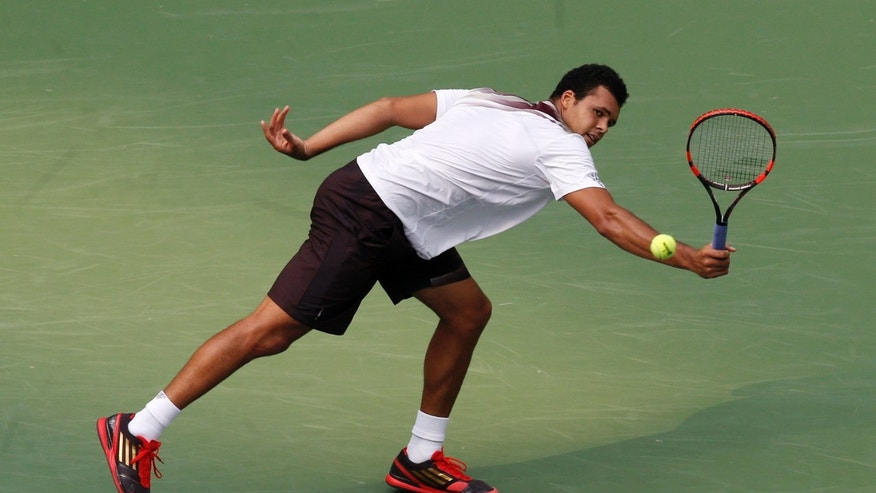Jo-Wilfried Tsonga of France returns a shot to Florian Mayer of Germany during the singles quarterfinal match of the Shanghai Masters tennis tournament at Qizhong Forest Sports City Tennis Center, in Shanghai, China, Friday, Oct. 11, 2013. Tsonga won 6-2, 6-3. (AP Photo/Eugene Hoshiko)