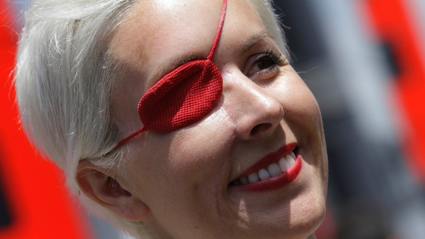 FILE - In this May 11, 2013 file photo, Spanish former F1 driver Maria De Villota smiles in the paddock at the Catalunya racetrack in Montmelo, near Barcelona, Spain. Spanish police have confirmed that racing driver Maria de Villota has been found dead in a hotel room in Seville, and say it appears she died of natural causes. She was 33. In July 2012, De Villota crashed while test driving a car for F-1 team Marussia. She lost her right eye in the accident. (AP Photo/Luca Bruno, File)