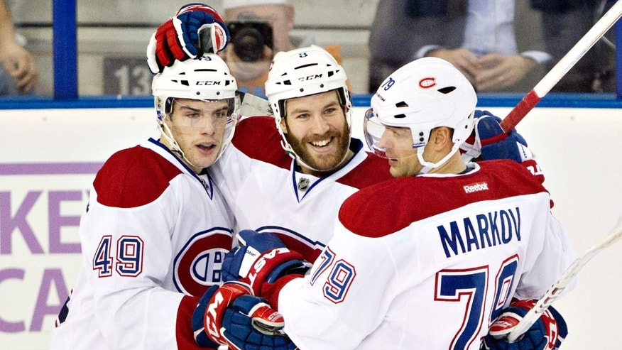 Montreal Canadians Michael Bournival (49), Brandon Prust (8) and Andrei Markov (79) celebrate a goal against the Edmonton Oilers during second-period NHL hockey game action in Edmonton, Alberta, Thursday, Oct. 10, 2013. (AP {Photo/The Canadian Press, Jason Franson)