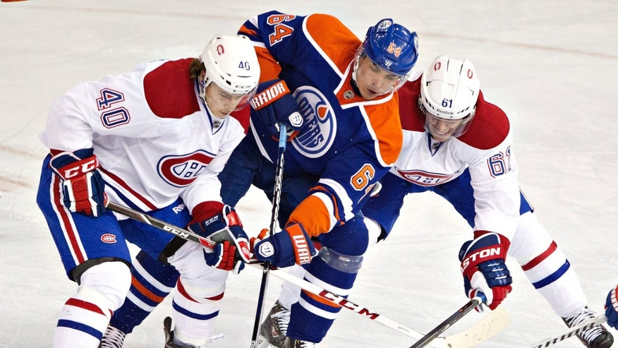 Montreal Canadians' Nathan Beaulieu (40) and Raphael Diaz (61) battle for the puck with Edmonton Oilers' Nail Yakupov (64) during second-period NHL hockey game action in Edmonton, Alberta, Thursday, Oct. 10, 2013. (AP {Photo/The Canadian Press, Jason Franson)