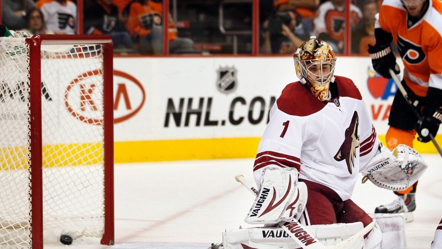 A puck hit for a goal by Philadelphia Flyers' Max Talbot lays in the net behind Phoenix Coyotes goalie Thomas Greiss late in the second period of an NHL hockey game on Friday, Oct. 11, 2013, in Philadelphia. (AP Photo/Tom Mihalek)