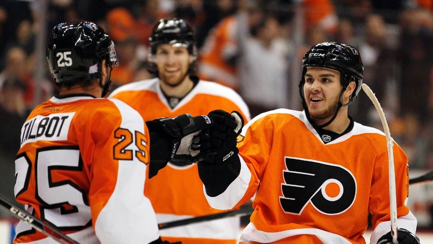 Philadelphia Flyers' Max Talbot, left, who scored, and Zac Rinaldo, right, who got the assist, tap gloves in the second period of an NHL hockey game against the Phoenix Coyotes, Friday, Oct. 11, 2013, in Philadelphia. (AP Photo/Tom Mihalek)