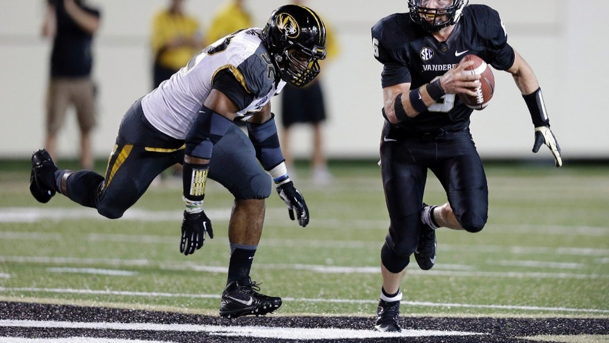 Missouri defensive lineman Michael Sam, left, chases Vanderbilt quarterback Austyn Carta-Samuels (6) in the fourth quarter of an NCAA college football game Saturday, Oct. 5, 2013, in Nashville, Tenn. Missouri won 51-28. (AP Photo/Mark Humphrey)