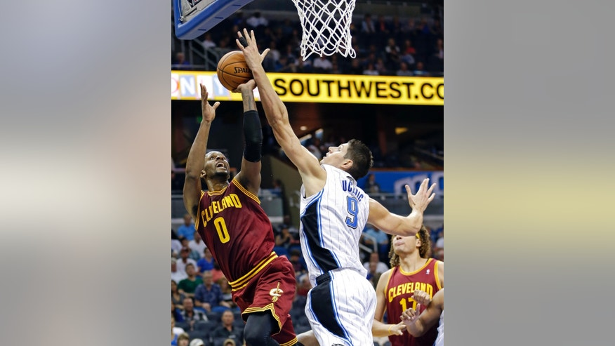 Orlando Magic's Nikola Vucevic (9), of Montenegro, blocks a shot-attempt by Cleveland Cavaliers' C.J. Miles (0) during the first half of an NBA preseason basketball game in Orlando, Fla., Friday, Oct. 11, 2013. (AP Photo/John Raoux)