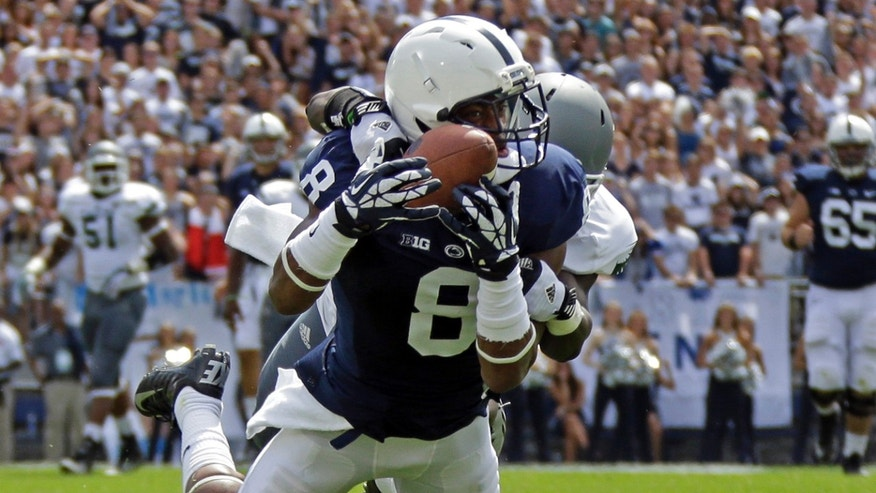 FILE- In this Sept. 7, 2013, file photo, Penn State wide receiver Allen Robinson (8) hauls in a 43-yard pass from quarterback Christian Hackenberg asith Eastern Michigan defensive back Willie Creear makes the tackle during the first quarter of an NCAA college football game in State College, Pa. With each new game, Robinson is seemingly landing in the program record books, and will be a key cog to a Penn State resurgence this season, if there is one. The Nittany Lions have lost two of three games, and will play host to No. 18 Michigan on Saturday. (AP Photo/Gene J. Puskar, File)