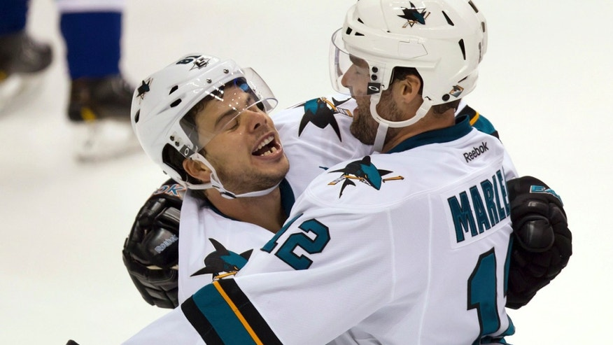 San Jose Sharks' Tyler Kennedy, left, and Patrick Marleau celebrate Marleau's goal against the Vancouver Canucks during the second period of an NHL hockey game in Vancouver, British Columbia, on Thursday, Oct. 10, 2013. (AP Photo/The Canadian Press, Darryl Dyck)