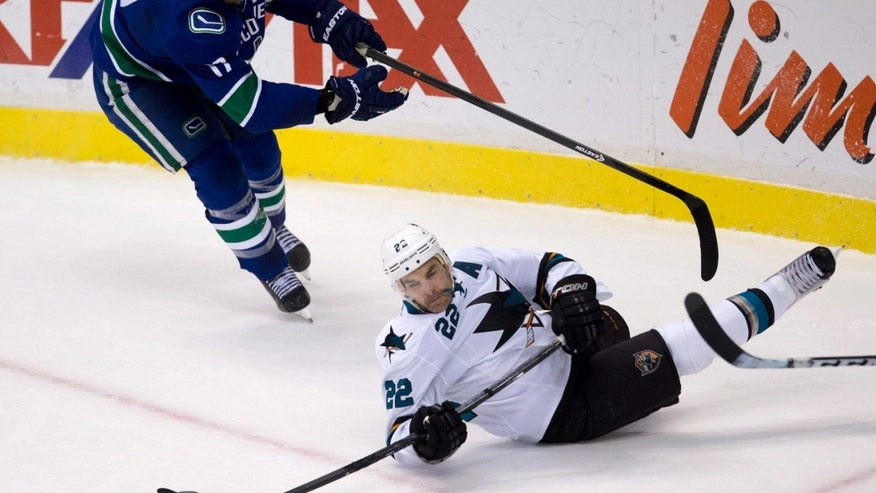 Vancouver Canucks' Ryan Kesler, left, trips San Jose Sharks' Dan Boyle and draws a penalty during the second period of an NHL hockey game in Vancouver, British Columbia, Thursday, Oct. 10, 2013.  (AP Photo/The Canadian Press, Darryl Dyck)