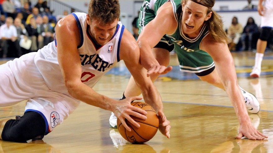 Philadelphia 76ers center Spencer Hawes (00) and Boston Celtics forward Kelly Olynyk vie for a loose ball in the first quarter of a preseason NBA basketball game Friday, Oct. 11, 2013, in Newark, Del. (AP Photo/Steve Ruark)