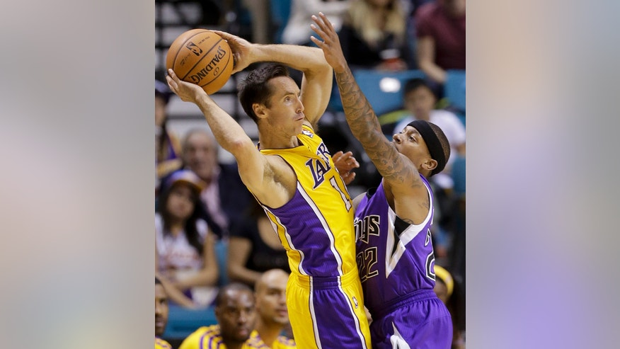 Los Angeles Lakers point guard Steve Nash (10) looks to pass against Sacramento Kings point guard Isaiah Thomas (22) in the first period of a preseason NBA basketball game, Thursday, Oct. 10, 2013, in Las Vegas. (AP Photo/Julie Jacobson)