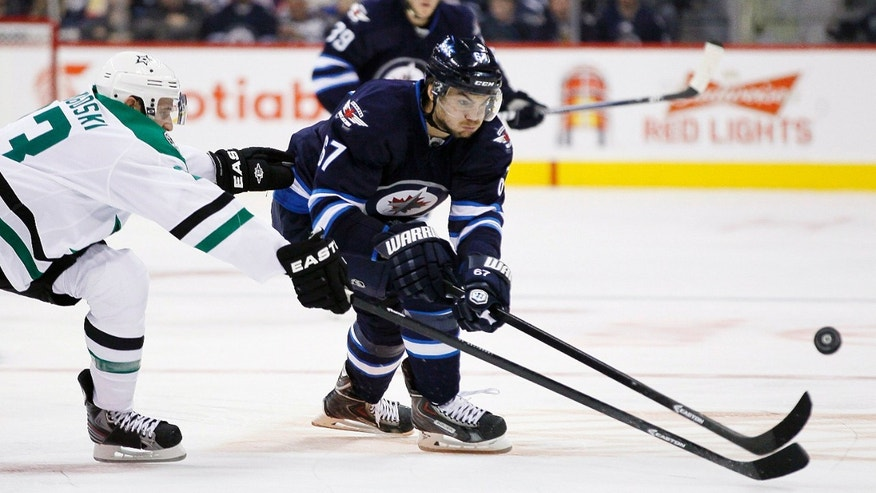 Winnipeg Jets' Michael Frolik (67) and Dallas Stars' Alex Goligoski, left, chase down the puck during second-period NHL hockey game action in Winnipeg, Manitoba, Friday, Oct. 11, 2013. (AP Photo/The Canadian Press, John Woods)