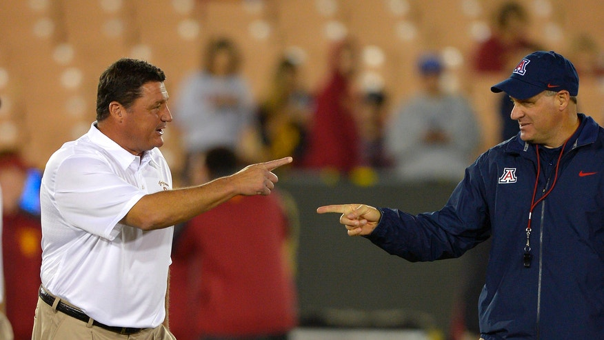 Southern California interim coach Ed Orgeron, left, talks with Arizona coach Rich Rodriguez prior to an NCAA college football game, Thursday, Oct. 10, 2013, in Los Angeles. (AP Photo/Mark J. Terrill)
