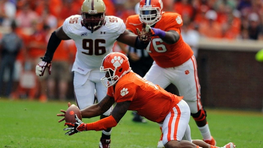 Clemson quarterback Tajh Boyd, center, recovers his own fumble while pursued by Boston College's Kaleb Ramsey (96) during the first half of an NCAA college football game on Saturday, Oct. 12, 2013, in Clemson, S.C. (AP Photo/ Richard Shiro)