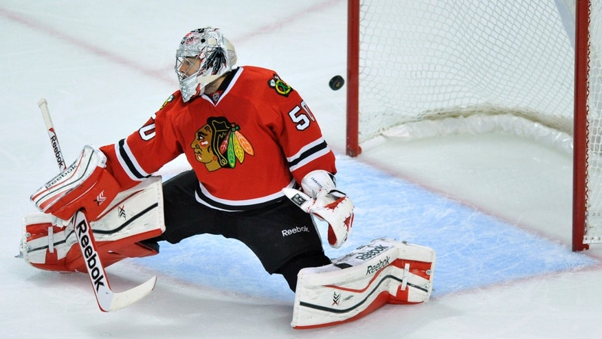Chicago Blackhawks goalie Corey Crawford makes a save during the first period of an NHL hockey game against the Buffalo Sabres in Chicago, Saturday, Oct. 12, 2013. (AP Photo/Paul Beaty)