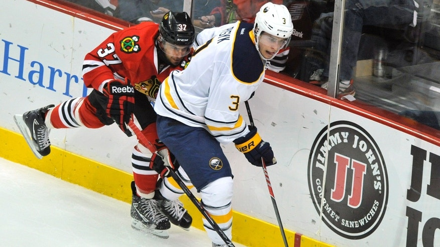 Chicago Blackhawks' Brandon Pirri (37), battles Buffalo Sabres' Mark Pysyk (3), for the puck during the second period of an NHL hockey game  in Chicago, Saturday, Oct. 12, 2013. Chicago won 2-1. (AP Photo/Paul Beaty)