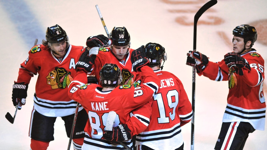 Chicago Blackhawks' Patrick Kane (88), celebrates with teammates Jonathan Toews (19), Andrew Shaw (65), Patrick Sharp (10), and Duncan Keith (2), after scoring a goal during the second period of an NHL hockey game against the Buffalo Sabres in Chicago, Saturday, Oct. 12, 2013. (AP Photo/Paul Beaty)