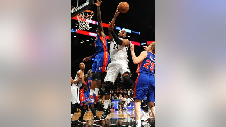 Brooklyn Nets' Paul Pierce (34) grabs a rebound over Detroit Pistons' Josh Smith (6) and Kyle Singler (25) in the first half of a preseason NBA basketball game Saturday, Oct. 12, 2013, in New York. (AP Photo/Kathy Kmonicek)