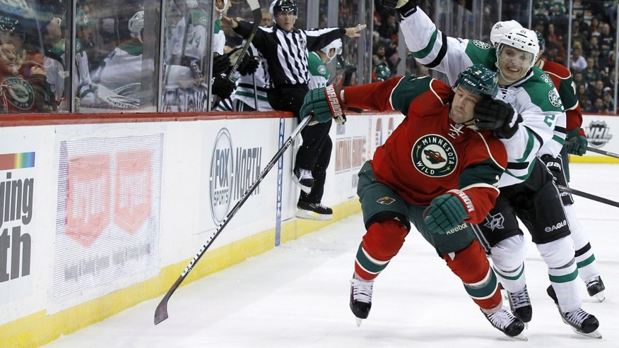 Minnesota Wild defenseman Keith Ballard, right front, gets tangled with Dallas Stars left wing Antoine Roussel (21) during the second period of an NHL hockey game in St. Paul, Minn., Saturday, Oct. 12, 2013. (AP Photo/Ann Heisenfelt)