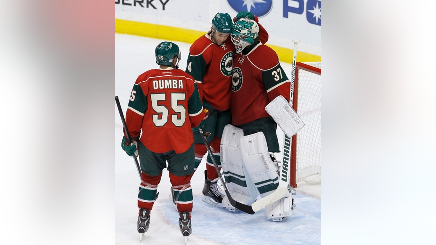 Minnesota Wild defenseman Clayton Stoner, center, and defenseman Mathew Dumba (55) celebrate with goalie Josh Harding (37) after the Wild defeated the Dallas Stars 5-1 in an NHL hockey game in St. Paul, Minn., Saturday, Oct. 12, 2013.  (AP Photo/Ann Heisenfelt)
